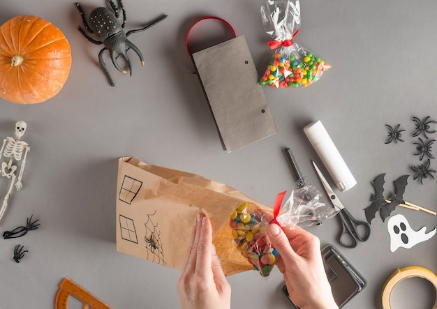 Step-by-step wrapping of a gift for halloween, flat lay. pack all the sweets and candies