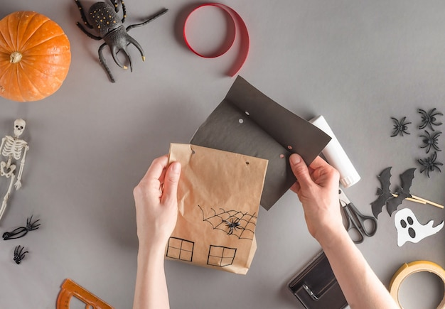 Step-by-step wrapping of a gift for halloween, flat lay.  returning the paper roof to the house