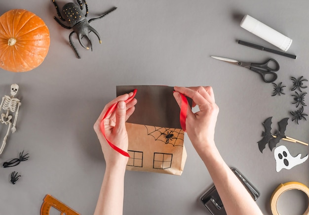 Step-by-step wrapping of a gift for halloween, flat lay. threading the tape through the holes on the roof