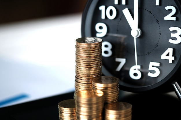 Step of coins stacks and alarm clock with tablet computer and financial graph