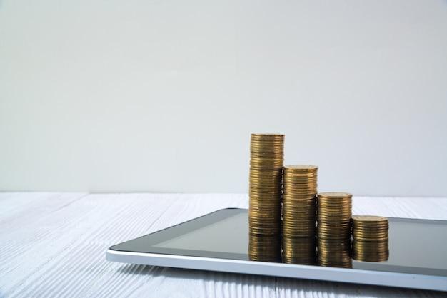 Шаг стога монетки на экран планшета на белой концепции таблицы, дела и финансов деятельности.