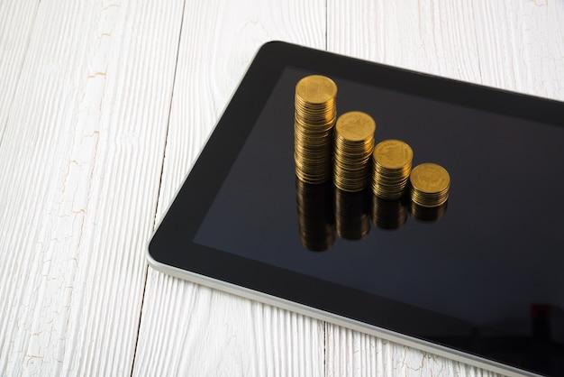 Шаг стопки монет на экране планшетного компьютера