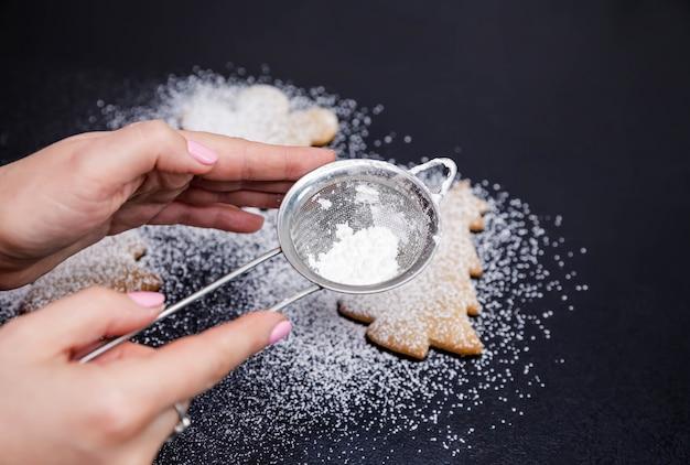 黒い石のカウンタートップに散らばった粉砂糖のステップ