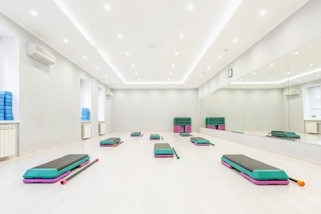 Степ-платформа в большом, светлом, пустом зале для аэробики. активный образ жизни и спорт.