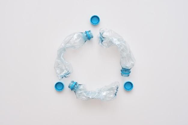 グリーンライフへのステップ。しわくちゃのペットボトルの孤立した円。廃棄物管理とリサイクル。ごみの分別の概念