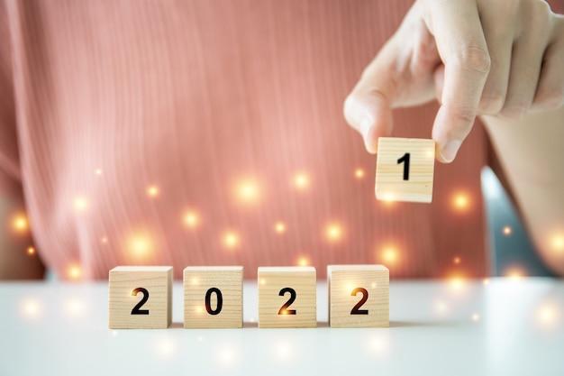 나무 블록 사다리에 올라 2022년 새해 축하를 위해 2022라는 단어를 배치했으며, 알아볼 수 없는 젊은 여성이 2022년을 보여주는 나무 블록을 배치했습니다.