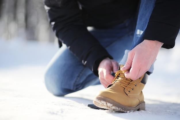Шаги по заснеженной тропе. мужчина гуляет по парку зимой.