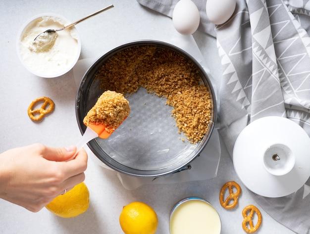 Шаги по приготовлению простого лимонного пирога с крекерами и кремовой начинкой. женская рука кладет молотые крекеры на форму для выпечки.