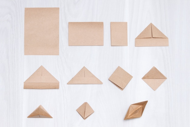 Steps of making origami paper boat on white wooden background.