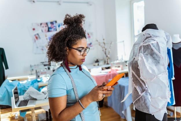 생성 단계. 덮여 더미에 대한 그녀의 손에 태블릿과 함께 머물 곱슬 전문 여성 디자이너