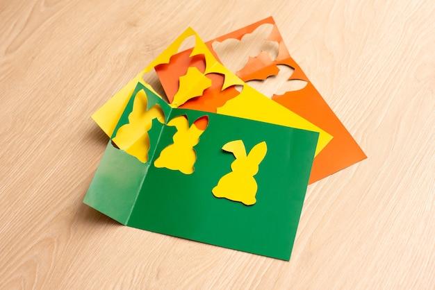 Шаги по вырезанию кроликов из бумаги для вырезок разных цветов.