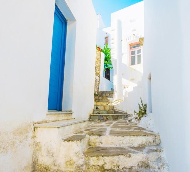 青い木製のドアで白塗りの壁の間の狭い通路をステップアップ