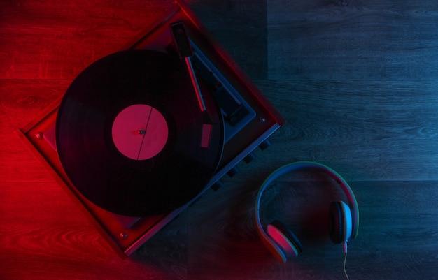 青赤のネオンライトが付いている木の床のステレオヘッドフォンおよびレトロなビニールレコードプレーヤー
