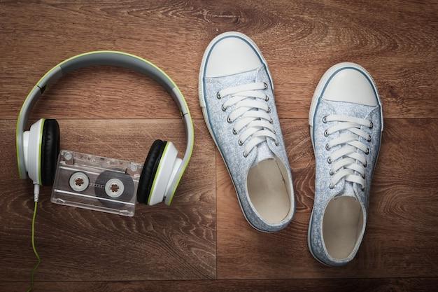 나무 바닥에 스테레오 헤드폰, 오디오 카세트 및 운동화. 레트로 미디어