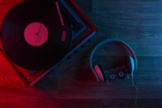 Stereo headphones and retro vinyl record player on a wooden floor with blue-red neon light