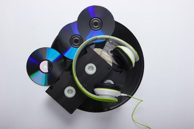 Stereo headphones, video cassettes, vinyl records, audio cassette, cd discs on a white surface