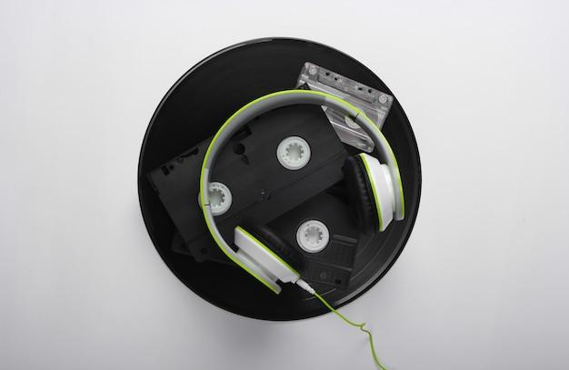 Stereo headphones, video cassettes, vinyl records, audio cassette on a white surface
