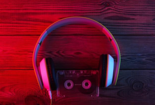 Стереонаушники с аудиокассетой на деревянной поверхности. неоновый красный и синий свет