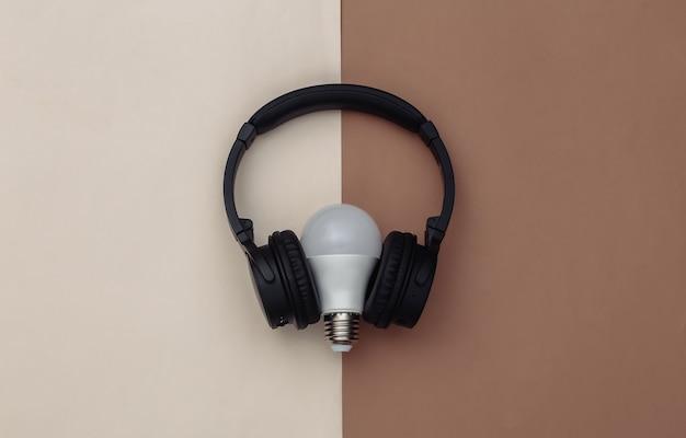 茶色のベージュの背景に電球付きのステレオヘッドフォン。上面図