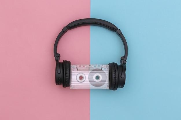ピンクブルーの背景にレトロなオーディオカセットを備えたステレオヘッドフォン。上面図