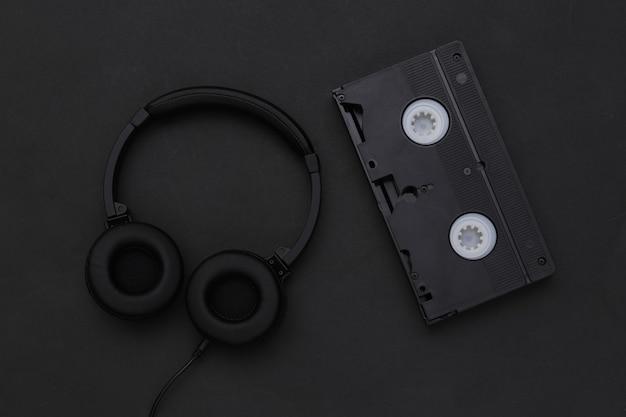 黒の背景にビデオカセット付きのステレオヘッドフォン。上面図