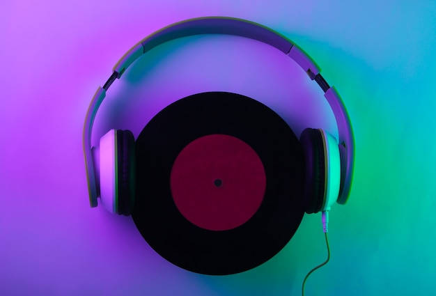 Stereo headphones with a vinyl record. neon, holographic light