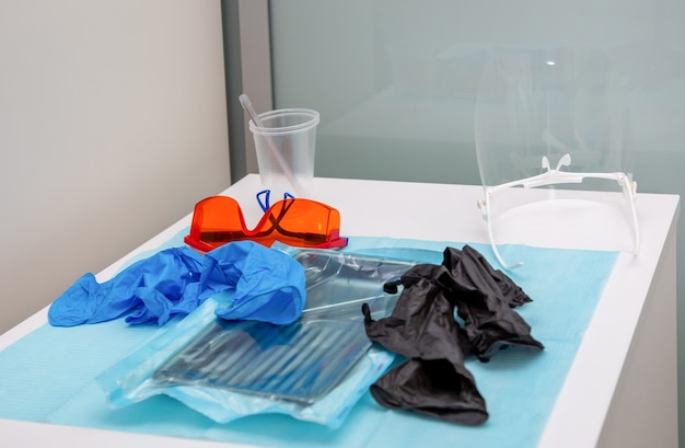 Sterile medical instruments in packaging and blue and black disposable gloves in a medical office