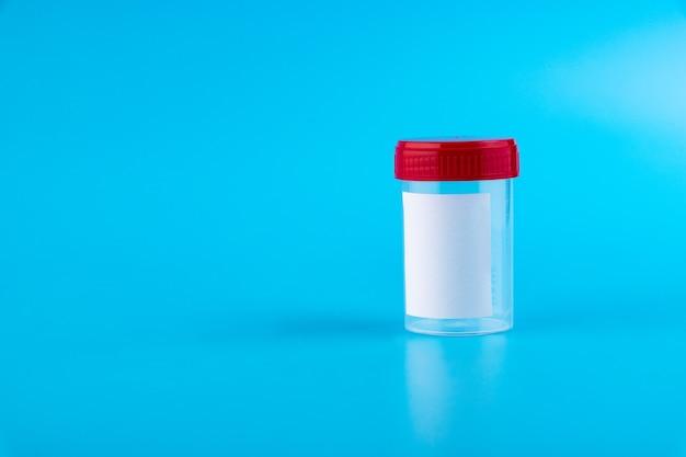 分析用の滅菌透明ブランクプラスチック容器。赤いふた。生体材料用の無菌医療容器。青い背景で隔離。
