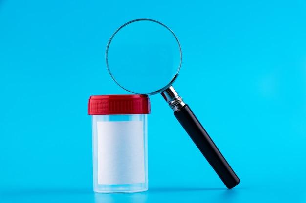 拡大鏡付きの滅菌透明空プラスチック分析容器。赤いふた生体材料用の滅菌医療容器。青い背景で隔離。