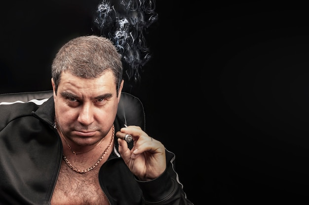 A stern adult man smoking a cigar looks seriously. copyspace. a crime boss, a mobster serving time in prison