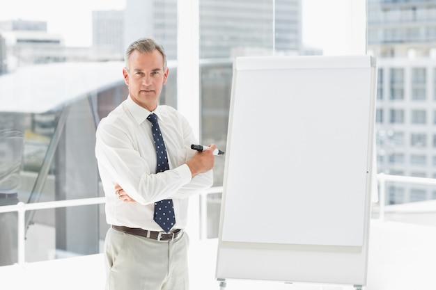 ホワイトボード、マーカーで立っているスターンのビジネスマン