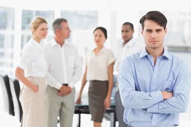 彼の後ろにチームと一緒に立っているスターンのビジネスマン