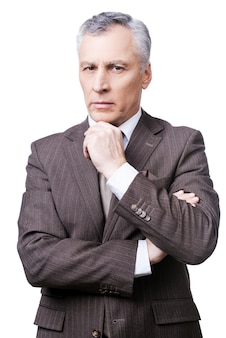 Stern glance of director. thoughtful mature man in formalwear holding hand on chin and looking at camera while standing against white background