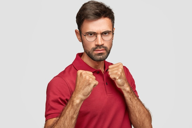 Stern serious unshaven male keeps hands in fists, ready to fight with competitor, looks under eyebrows, has displeased expression, dressed in casual red t-shirt, stands against white wall indoor