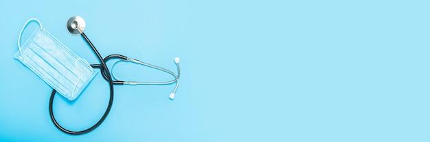 医療stestoscopeと青色の背景に防護マスク。コンセプト医学、看護師、病院、安全、流行。