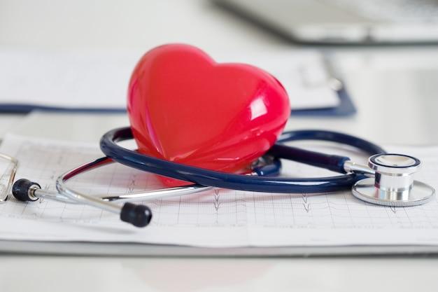 心電図に横たわっているstethescopeと赤いハート。ヘルスケア、心臓病学および医療の概念