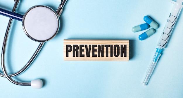 聴診器、注射器と丸薬、そして予防という言葉が書かれた木製のブロック
