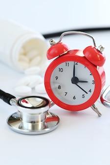 聴診器、目覚まし時計、白い錠剤のクローズアップ。健康管理