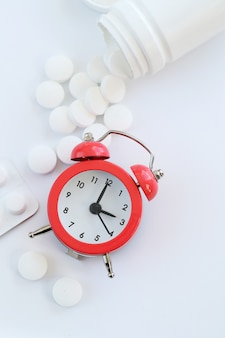 Stethoscope, alarm clock and white pills closeup. healthcare