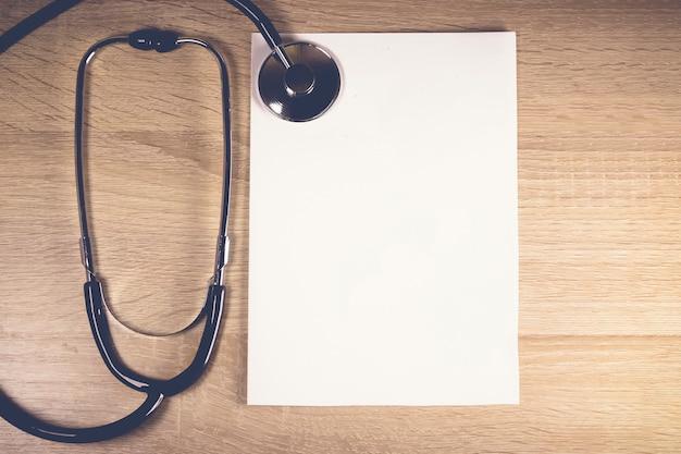 聴診器とあなたのテキストのためのコピースペースが付いている木の背景の上の一枚の紙。ヘルスケアの概念。ヘルスケアおよび医療機器。健康診断と診断。医師の義務。