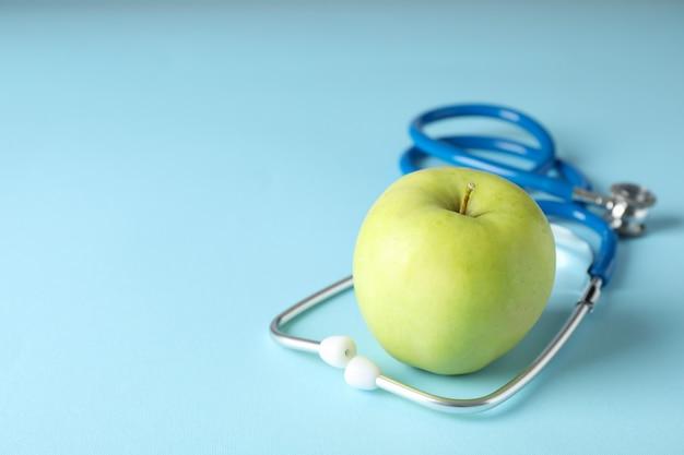 Стетоскоп и яблоко на голубой предпосылке, конце вверх. здравоохранение