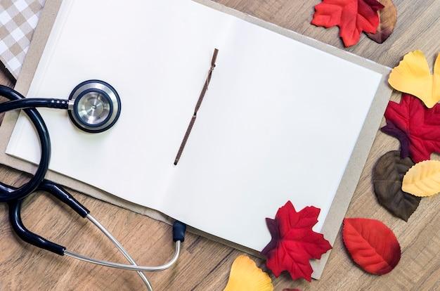 Стетоскоп и пустой белый записная книжка на деревянном столе