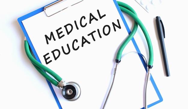 聴診器と白い表面に分離されたワークシートに医学教育のテキストと青いクリップボード