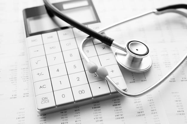 聴診器と電卓。医療費または医療保険の概念