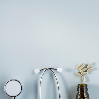Stethoscope and capsules above the bottle over the grey background