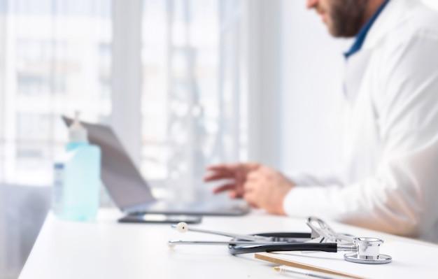 Стетоскоп и доска с зажимом на столе врачей на заднем плане. врач проводит онлайн-консультацию пациента с помощью ноутбука. концепция онлайн-медицины