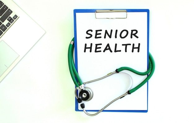 白い紙とコピースペースにseniorhealthのテキストが書かれた聴診器とクリップボード。