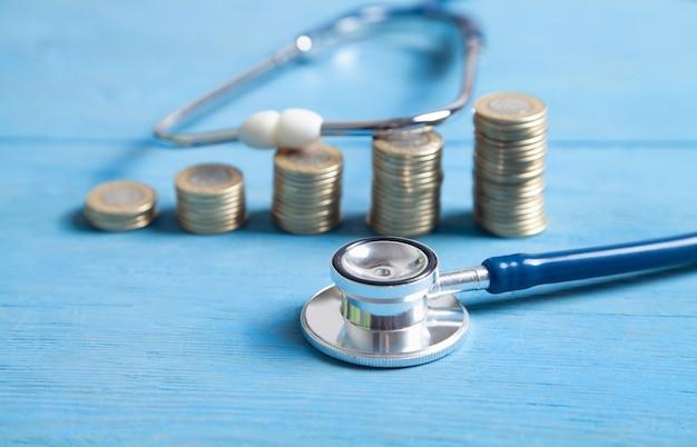 青い背景に聴診器とコイン。