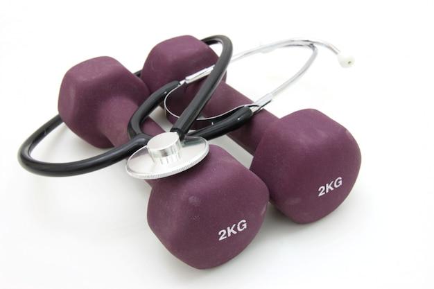 健康的なライフスタイルを概念化するための聴診器とダンベルトレーニングウェイトの組み合わせ。