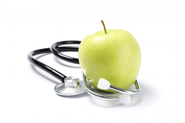 Стетоскоп и зеленое яблоко, изолированные на белой поверхности